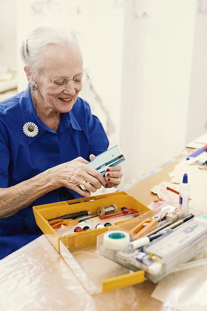 """H.M. Dronningen er meget glad for sin gamle, gule værktøjskasse og passer rigtig godt på den: """"Alt, der kan klares med saks og lim, tape og hæfteklammer, det er lige mig."""" Værktøjskassen bruges bl.a., når Dronningen klippe-klistrer papirhatte. Foto: Kamilla Bryndum"""