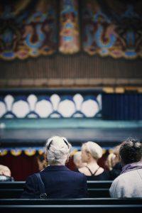 H.M. Dronningen er tilskuer på Pantomimeteatret i Tivoli. Med andre medvirkende sidder scenografen spændt og venter på, at tæppet går til en prøve på den kommende forestilling. Foto: Kamilla Bryndum