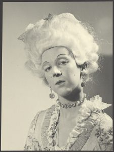"""H.M. Dronningen som 14-årig prinsesse, sminket næsten til uigenkendelighed og trådt ind i rollen som fin og fornem dronning fra 1700-tallet. Billedet er fra en forestilling i det private Juliane Marie Teatret, som H.M. Dronningen og hendes søstres barnepige satte i værk for Prinsesserne og deres venner på Fredensborg Slot i 1954. H.M. Dronningen er udklædt som dronning Juliane Marie med kunstig næse og paryk samt ægte juveler fra Dronning Ingrids """"udlånsmarked"""". Foto: H.M. Dronningens Håndbibliotek"""